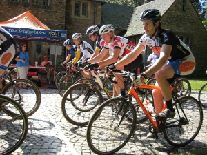 Men's category 3 racers leave the start/finish on the cobbles in front of the Hanes' mansion.