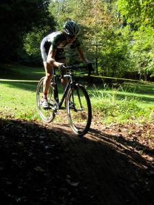 Women's Pro/Category 1,2,3 racer crests a knoll before dropping into the woods.
